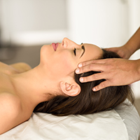 Young caucasian smiling woman receiving a head massage in a spa center with eyes closed. Female patient is receiving treatment by professional therapist.